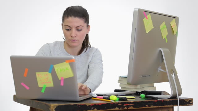 Stressed young woman working on pc and laptop simultaneous. video