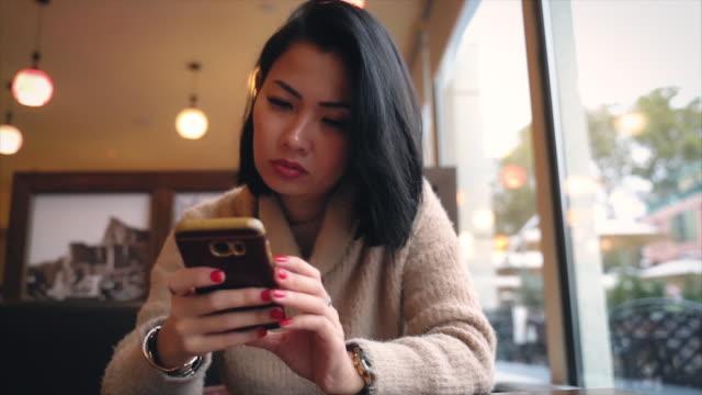 stockvideo's en b-roll-footage met stressvolle aziatische vrouw het verzenden van sms-berichten via mobiele telefoon - daten