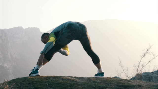 Stretching exercises on top of the mountain video