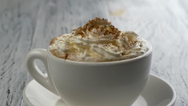 streuartikel zimtpulver in kaffee cappuccino-tasse. im alter von weißem holz hintergrund - cappuccino stock-videos und b-roll-filmmaterial