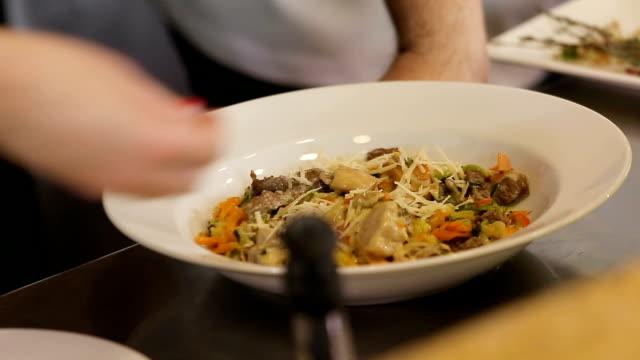 vidéos et rushes de strewing parmesan aux pâtes végétales - parmesan