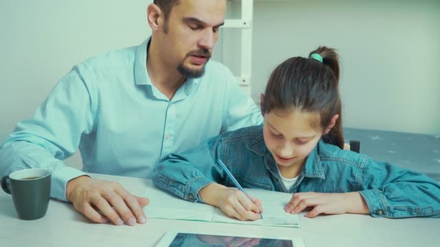 strict father is angry with his daughter doing homework