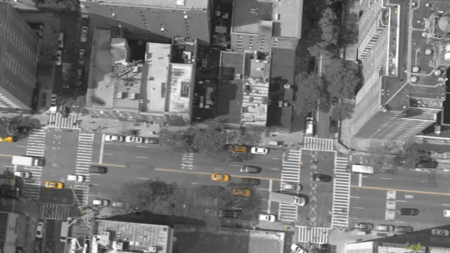 AERIAL TOP DOWN: Striking yellow cabs stand out in cinematic gray cityscape. video