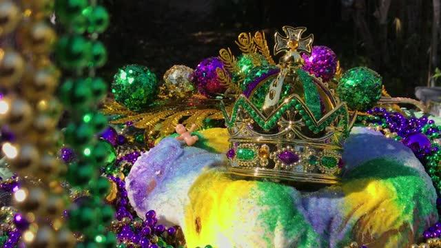 vidéos et rushes de chaînes de perles encadrant le gâteau roi de mardi gras avec la couronne et le bébé minuscule entouré par des perles colorées - galette des rois