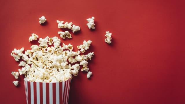 vídeos de stock, filmes e b-roll de caixa listrada com pipoca para a noite do filme - balde pipoca