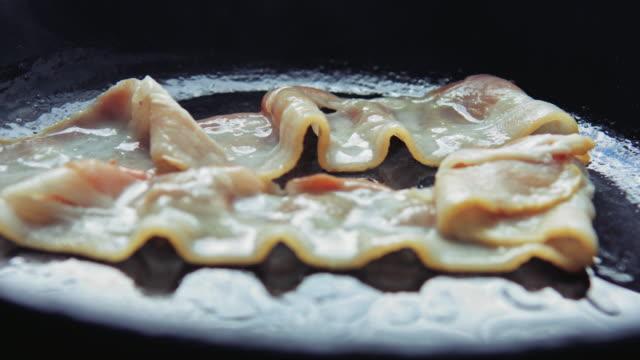 vídeos de stock, filmes e b-roll de bacon frito tiras frito em uma panela. - dieta paleo