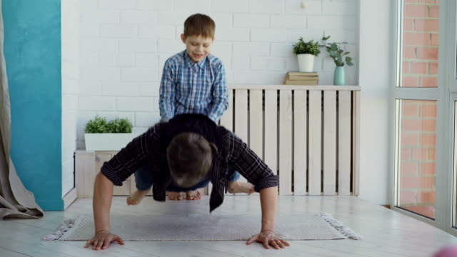 Strong active man is doing push-ups with his laughing little son sitting on his back. Sport, spending time with family, happy childhood concept. video