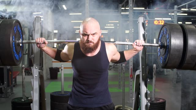strong active powerlifter attempting to lift heavy barbell row - man city exercise abs video stock e b–roll
