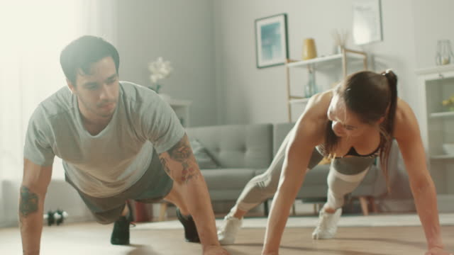 strong and beautiful athletic fitness couple in workout clothes doing push up exercises and giving each other a high five in their bright and spacious living room with minimalistic interior. - ćwiczyć filmów i materiałów b-roll
