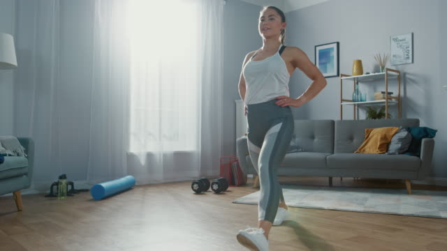 strong and beautiful athletic fitness girl in sportswear is doing forward lunge exercises in her bright and spacious living room with minimalistic interior. - edificio residenziale video stock e b–roll
