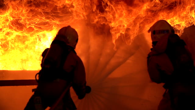 vídeos de stock e filmes b-roll de strong and brave firefighter on duty in burning building.two firefighters fighting a fire with a hose and water during a firefighting. - resgate
