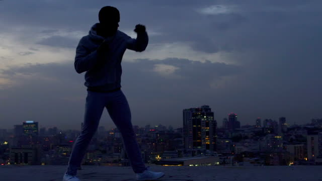 Strong and courageous guy fearlessly overcoming difficulties, shadow boxing