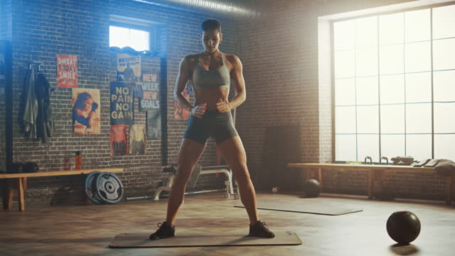 vídeos de stock e filmes b-roll de strong and fit beautiful athletic woman in sport top and shorts is doing squat exercises in a loft style industrial gym with motivational posters. it's part of her cross fitness training workout. - agachar se