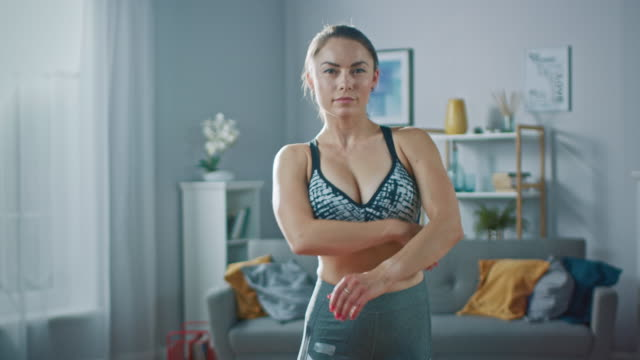 strong and fit beautiful busty girl in an athletic top is posing with a soft smile in her bright and spacious living room with minimalistic interior. - decolleté video stock e b–roll