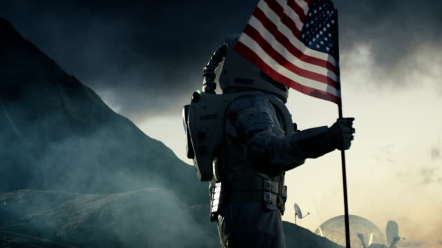 Strong Astronaut Walks with the Flag of Unites States of America on the Dark Alien Planet. Space Travel, Colonisation Theme. video