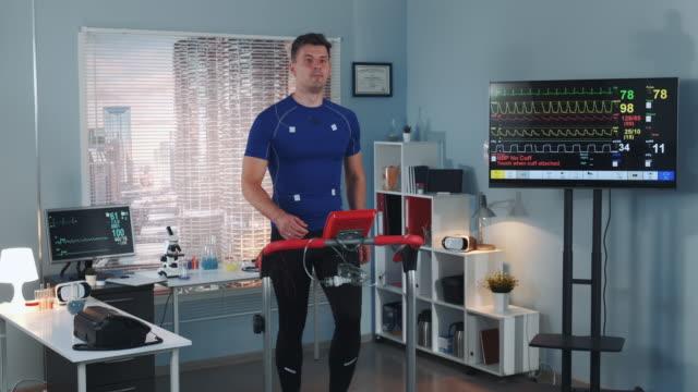 strong athlete doing cardiac stress test on racetrack - elektroda filmów i materiałów b-roll