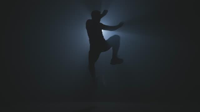 vídeos de stock, filmes e b-roll de o atleta forte bate pelo pé com salto na ginástica fumarento no movimento lento. boxer no ginásio. - artes marciais