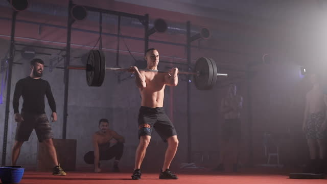 Strong athlete raises the bar with weight and holds it video