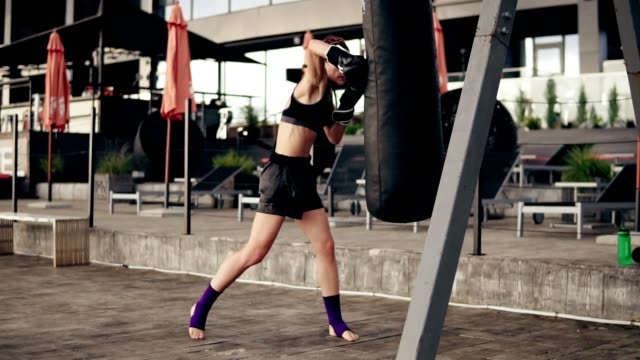 strong athletic female boxer in gloves exercising with a bag. workout outside. female boxer training. self defence concept. slowmotion shot - kick boxing video stock e b–roll