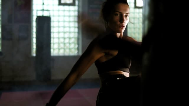 Strong athletic female kickboxer hits a boxing bag with her leg. She is exercising with a boxing bag in dark gym with smoke