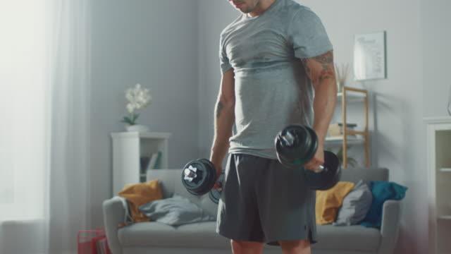 強い運動に合わせて男 t シャツとショート パンツでは広々 とした彼の家でダンベルふくらはぎを上げる練習をやって、ミニマルなインテリアで明るいアパートです。 - 耐久力点の映像素材/bロール