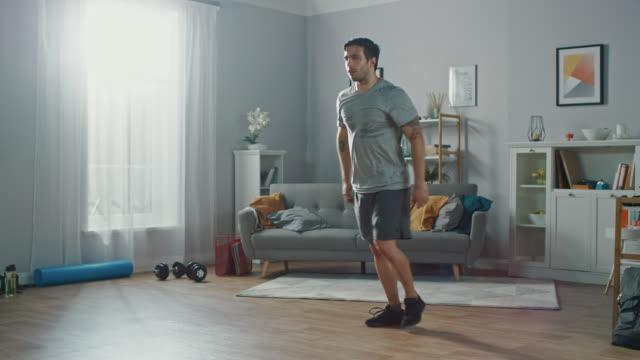 t-셔츠와 반바지에 강한 운동 맞는 남자 하 고 앞으로 돌진 연습 집에서 그의 넓고 최소한의 인테리어와 밝은 아파트에는. - 근육질 체격 스톡 비디오 및 b-롤 화면