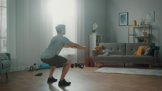 strong athletic fit man in t-shirt and shorts is doing squat exercises at home in his spacious and bright apartment with minimalistic interior. - ćwiczyć filmów i materiałów b-roll