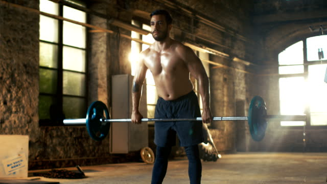 Strong Athletic Shirtless Man Lifts Heavy Barbell as a Part of  Fitness Training Routine. Gym is in Remodeled Factory. video