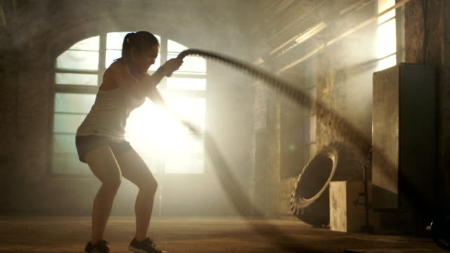 Strong Athletic Woman Exercises with Battle Ropes as Part of Her Fitness Gym Workout Routine. She's Covered in Sweat and Training Takes Place in a Abandoned Factory Remodeled into Gym.