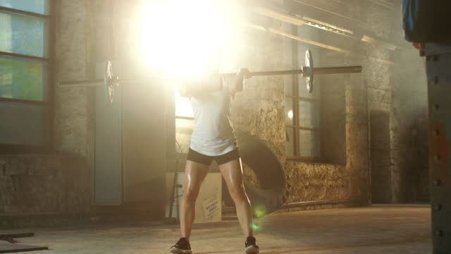 Strong Athletic Woman in Sportswear Lifts Heavy Barbell and Does Squats with it as a Part of Her Fitness Training Routine. Gym is in Remodeled Factory. video
