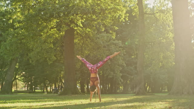 MS Strong, athletic young woman practicing yoga handstand in sunny, idyllic park