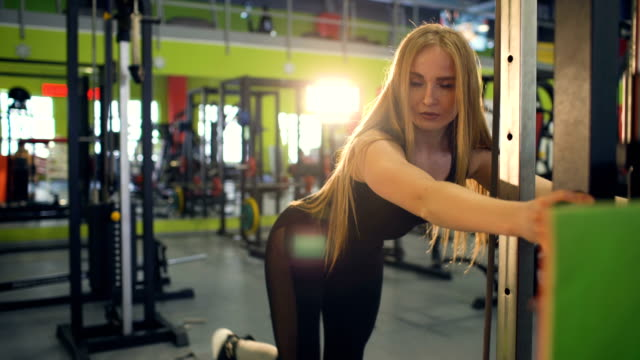 Strong blonde woman doing exercise wtiht lifting weights in fitnest club video