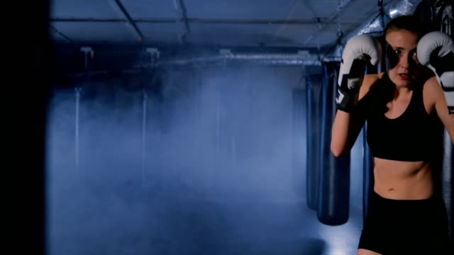 strong boxer girl fighting with shadow in a smoky gym - allenamento con l'ombra video stock e b–roll