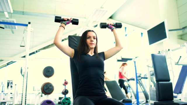 Strong brunette woman doing exercise in fitness club video