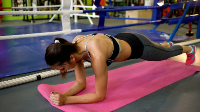 Strong brunette woman doing exercise in fitnest club video