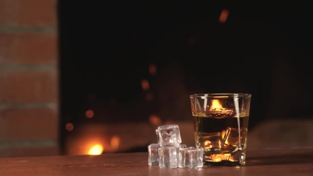 strong drink on background of bright sparks and burning flames in the fireplace. - scotch whisky video stock e b–roll