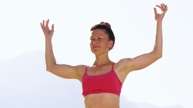 Strong fit woman standing in mudra posture outdoors