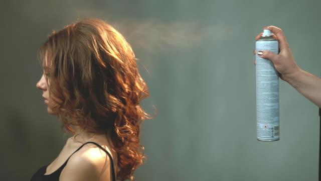 stockvideo's en b-roll-footage met sterke fixatie vernis. meisje zit en wacht totdat de stylist haar haar voltooit. - curly brown hair
