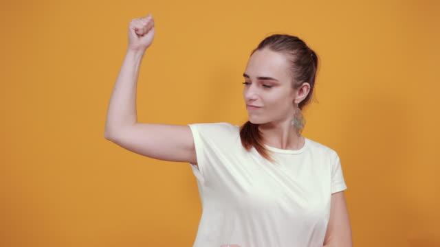 stockvideo's en b-roll-footage met strong girl toont haar biceps en de kracht die ze heeft. - gespierd
