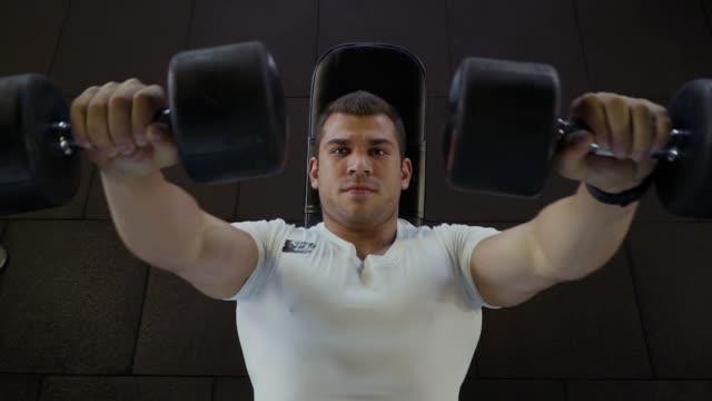 stockvideo's en b-roll-footage met sterke man maakt oefeningen met halters in de sportschool - wit t shirt