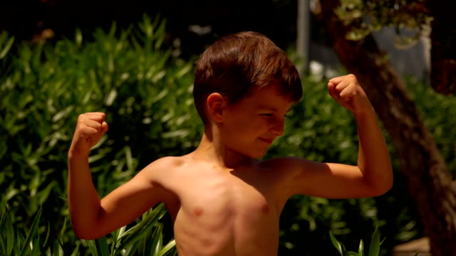 Strong little boy shows his muscle - video