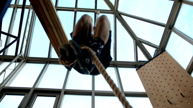 strong man climbing rope - inerpicarsi video stock e b–roll