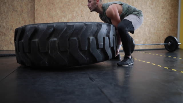 Strong Man Doing Tyre Flipping In Gym Strong Man Doing Tyre Flipping Work Out In Health Club cross training stock videos & royalty-free footage
