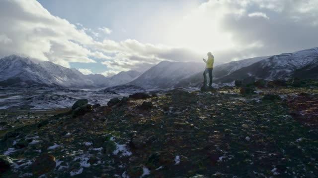 강한 남자 등산객 산 피크에서 스마트 폰과 사진 촬영. 놀라운 새벽. - mountain top 스톡 비디오 및 b-롤 화면