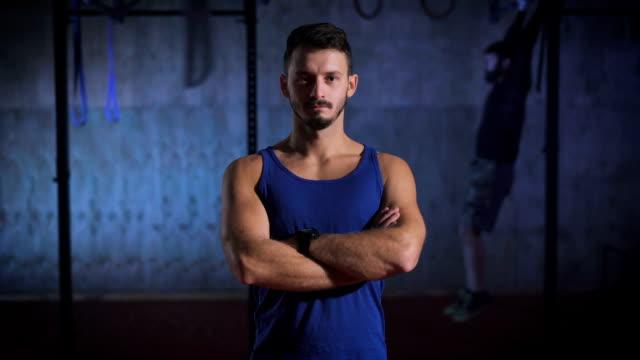 Hombre fuerte en camisa azul con los brazos cruzados posando en el gimnasio - vídeo