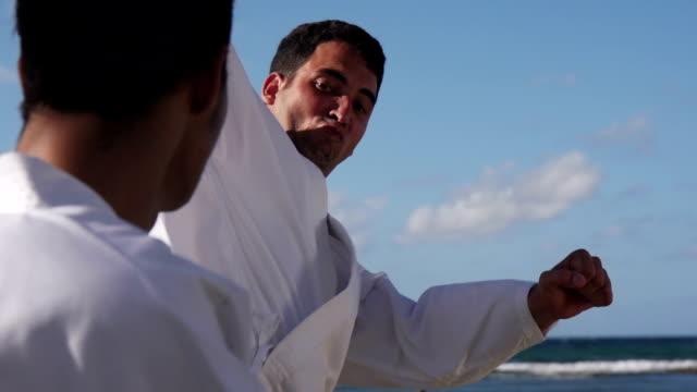 tekme ve deniz kenarında plajda mücadele güçlü adam - karate stok videoları ve detay görüntü çekimi