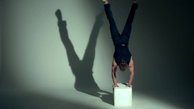 strong man performs handstand - top nero video stock e b–roll