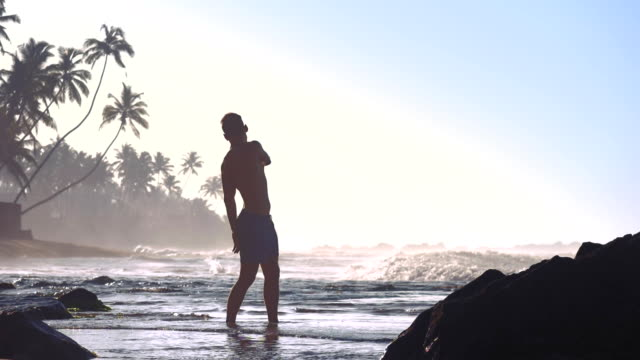 strong man silhouette turns stretching back on ocean coast