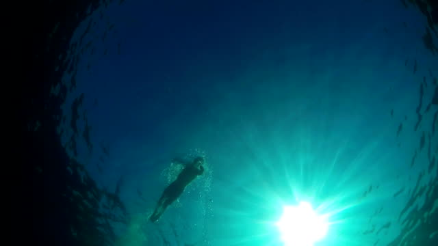 UNDERWATER LOW ANGLE: Strong man swimming front crawl in blue sea on sunny day video