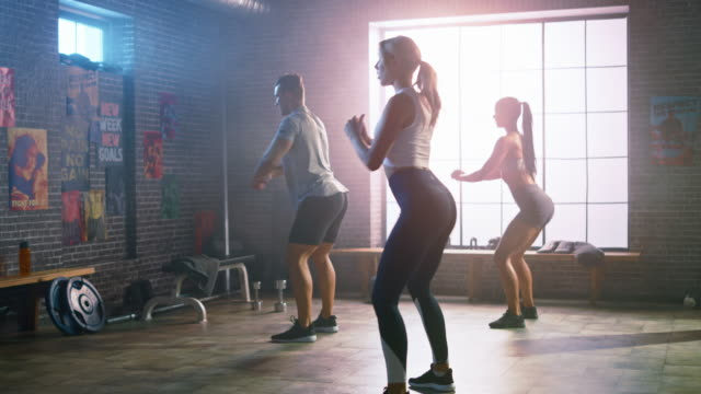 vídeos de stock e filmes b-roll de strong masculine man and two fit atletic women are doing squat exercises. they workout in a loft gym with motivational posters on walls. it's sunny and room has warm light. part of their team fitness. - agachar se